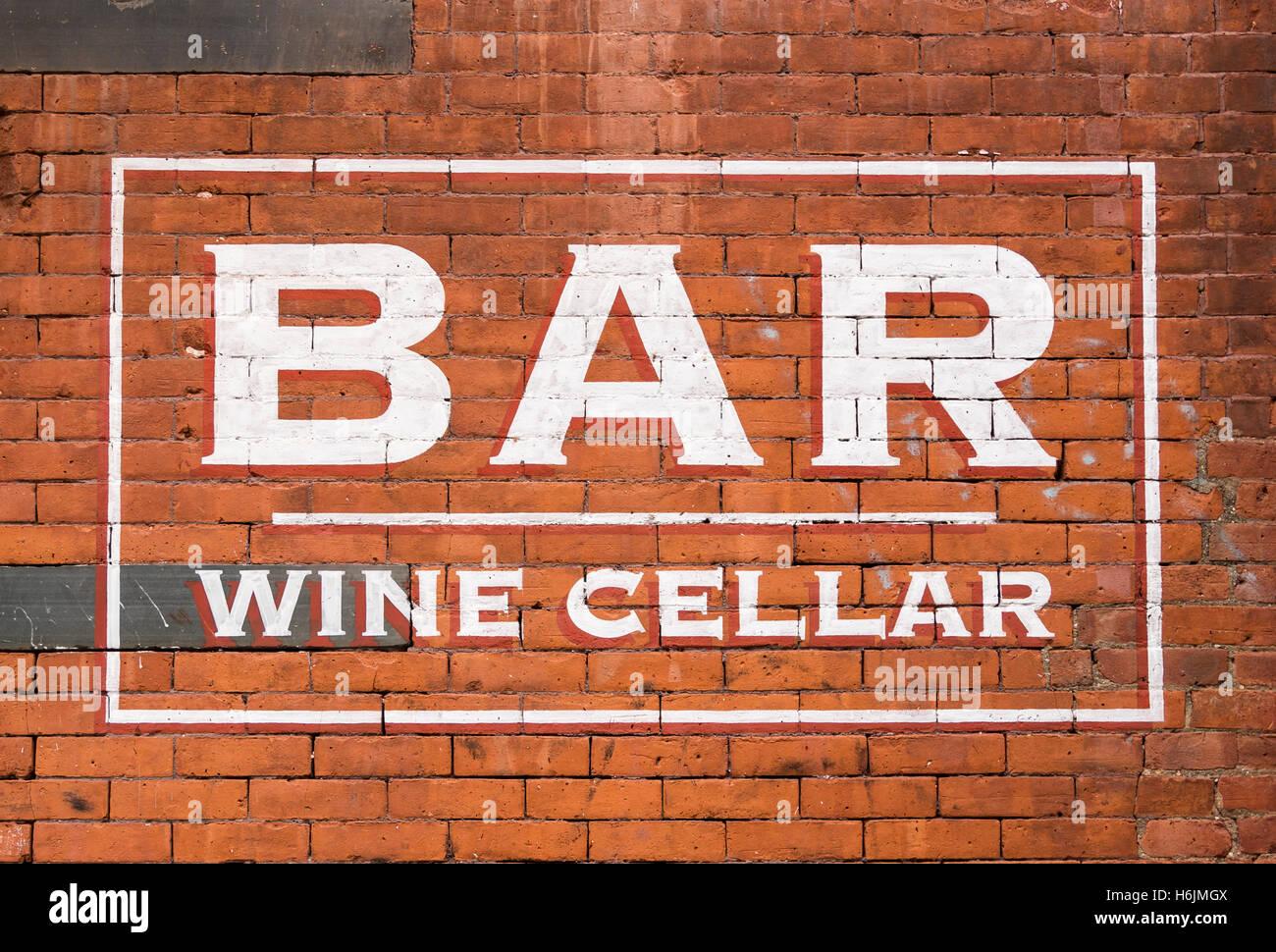 Cave A Vin En Brique peint panneau disant bar et cave à vin sur un mur de brique rouge