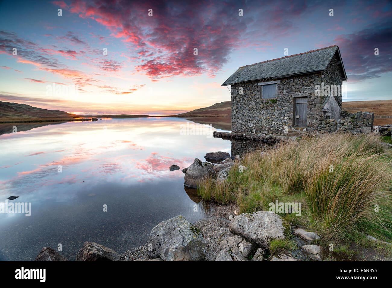 Coucher de soleil sur un ancien hangar à bateaux sur les rives du Devoke l'eau, un lac éloigné sur Birker est tombé dans le Lake District national par Banque D'Images