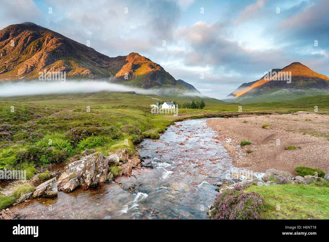 Le lever du soleil sur les sommets de l'éclairage à Glencoe dans les Highlands d'Ecosse Photo Stock