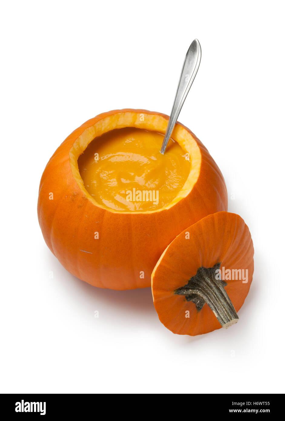 Soupe de potiron frais dans une citrouille orange sur fond blanc Photo Stock