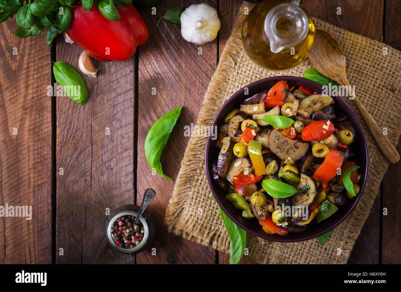 Petites aubergines ragoût épicé, poivrons, olives et câpres avec des feuilles de basilic. Vue Photo Stock