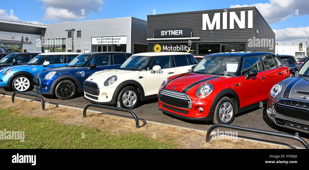 Concessionnaires de voitures d'affichage d'une ligne de seconde main colorée BMW Mini voitures sur parvis de Sytner Banque D'Images