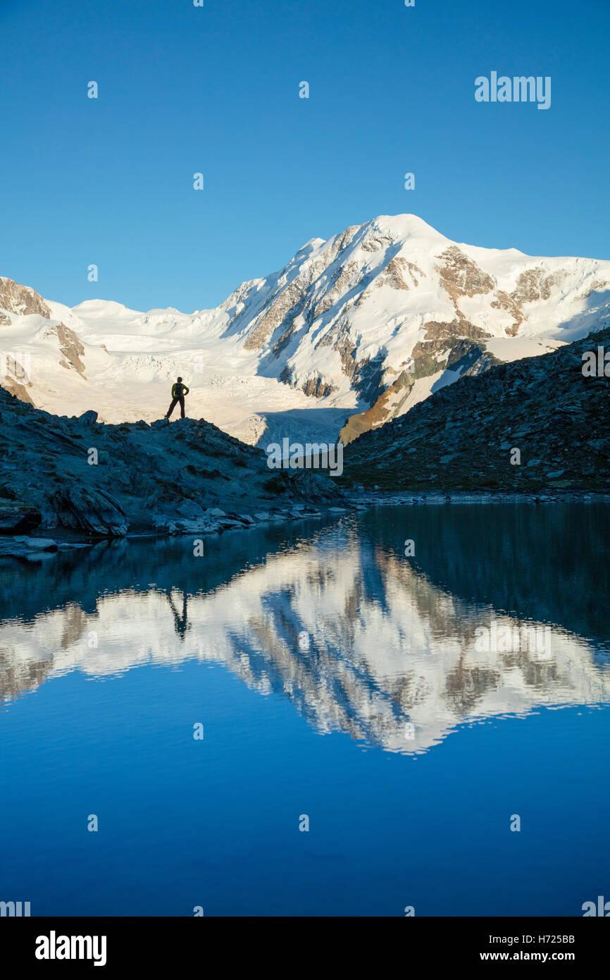 Randonneur et Lyskamm reflétée dans le, Riffelsee Alpes Pennines, Zermatt, Valais, Suisse. Photo Stock