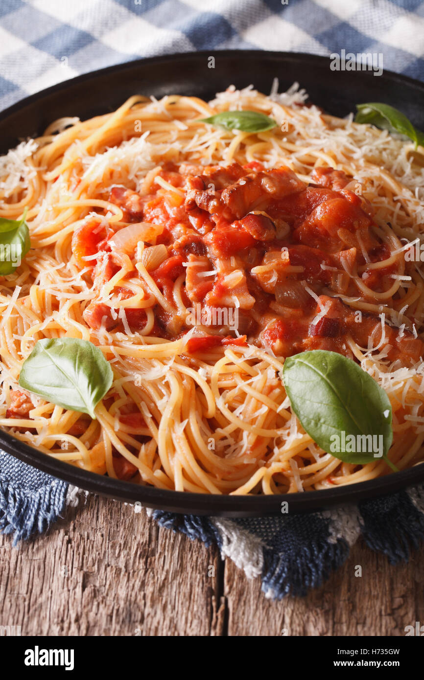 Spaghetti à l'amatriciana avec le fromage et le basilic close-up sur une plaque verticale sur la table. Photo Stock