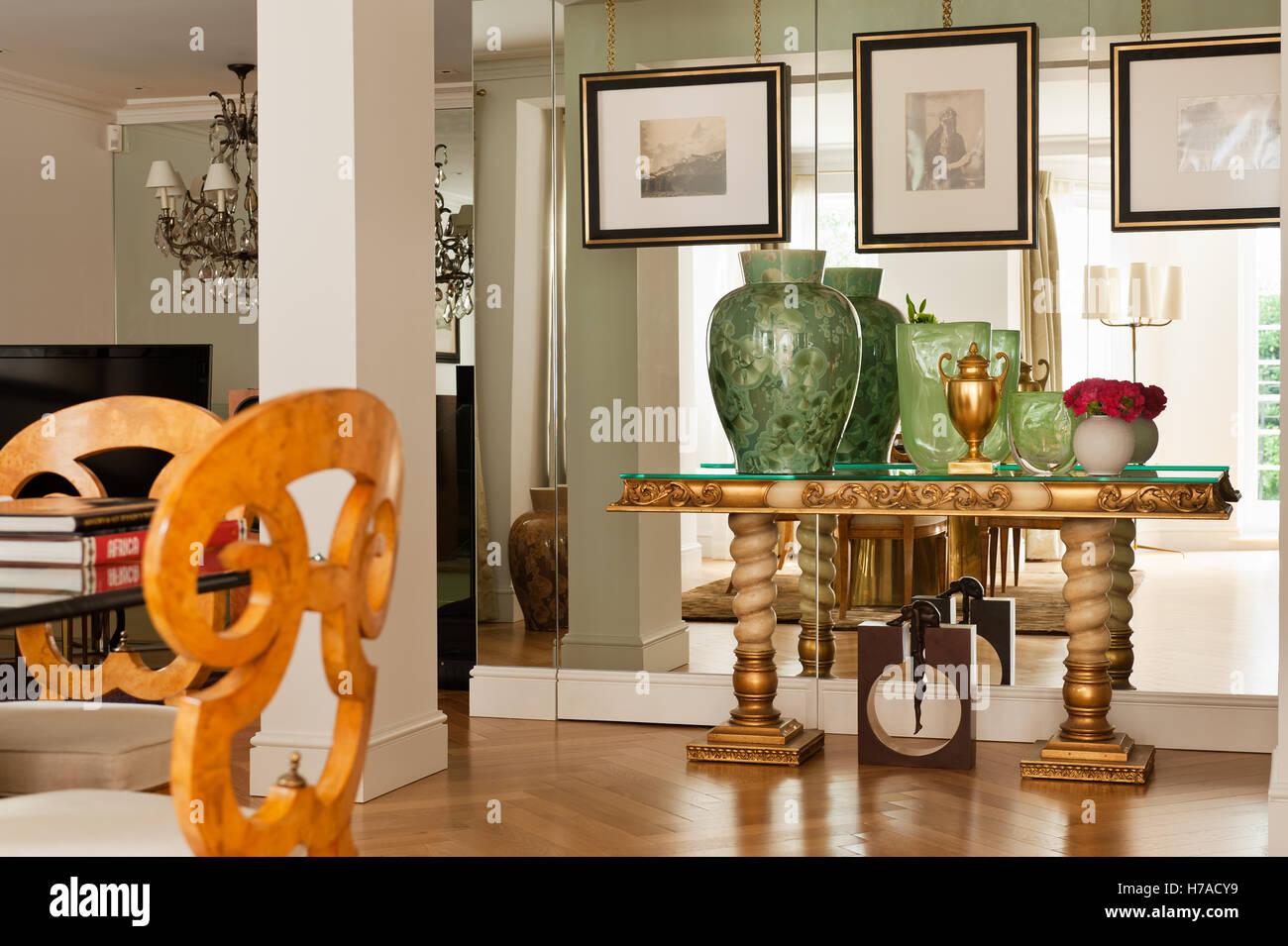 Verrerie vert or métallique sur console à miroir mural dans la salle de séjour avec le pilier en France Accueil Banque D'Images