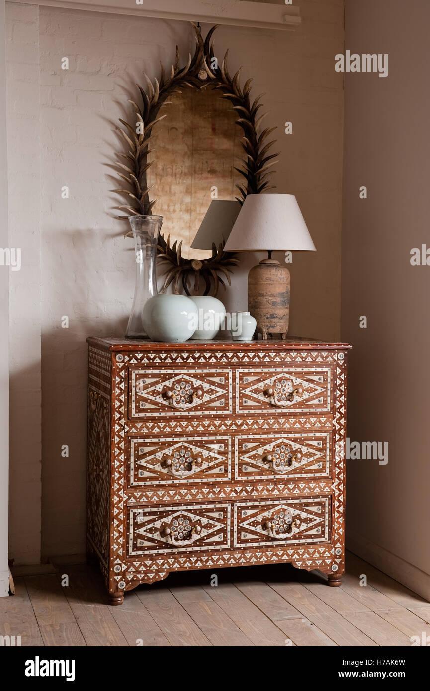 Commode à trois tiroirs en marqueterie d'os en dessous d'un miroir en andouiller de Guinevere antique Photo Stock