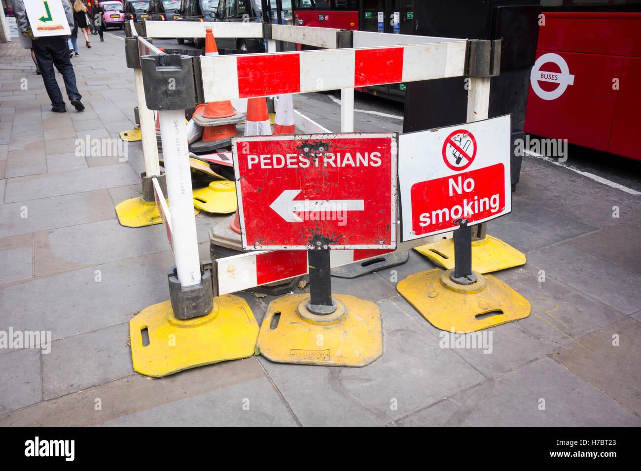 Travaux sur un trottoir à Londres, au Royaume-Uni avec des barrières et des panneaux Photo Stock