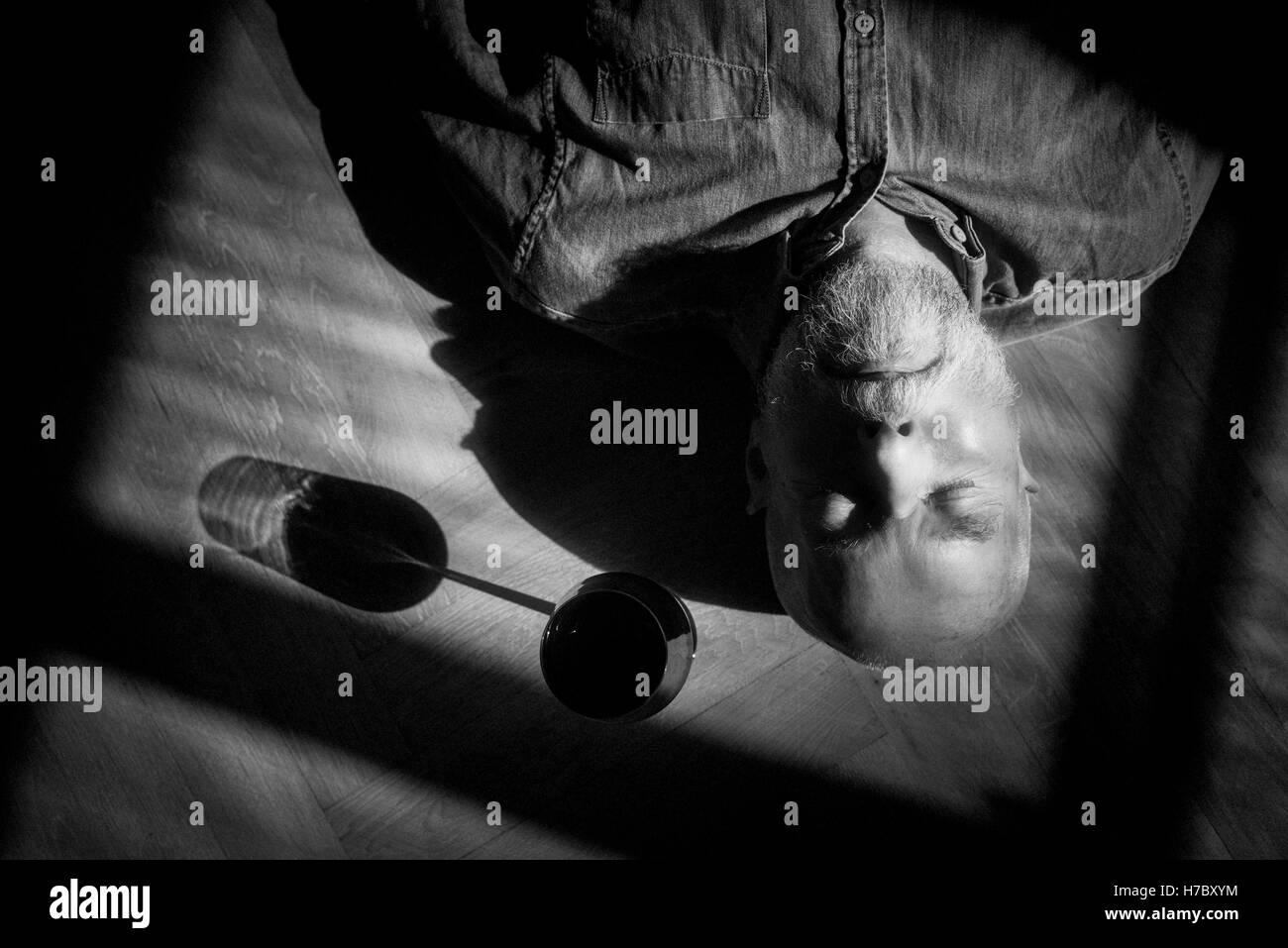 Vieil homme se reposant sur le sol. Portrait en noir et blanc avec des ombres profondes. Image conceptuelle de la Banque D'Images