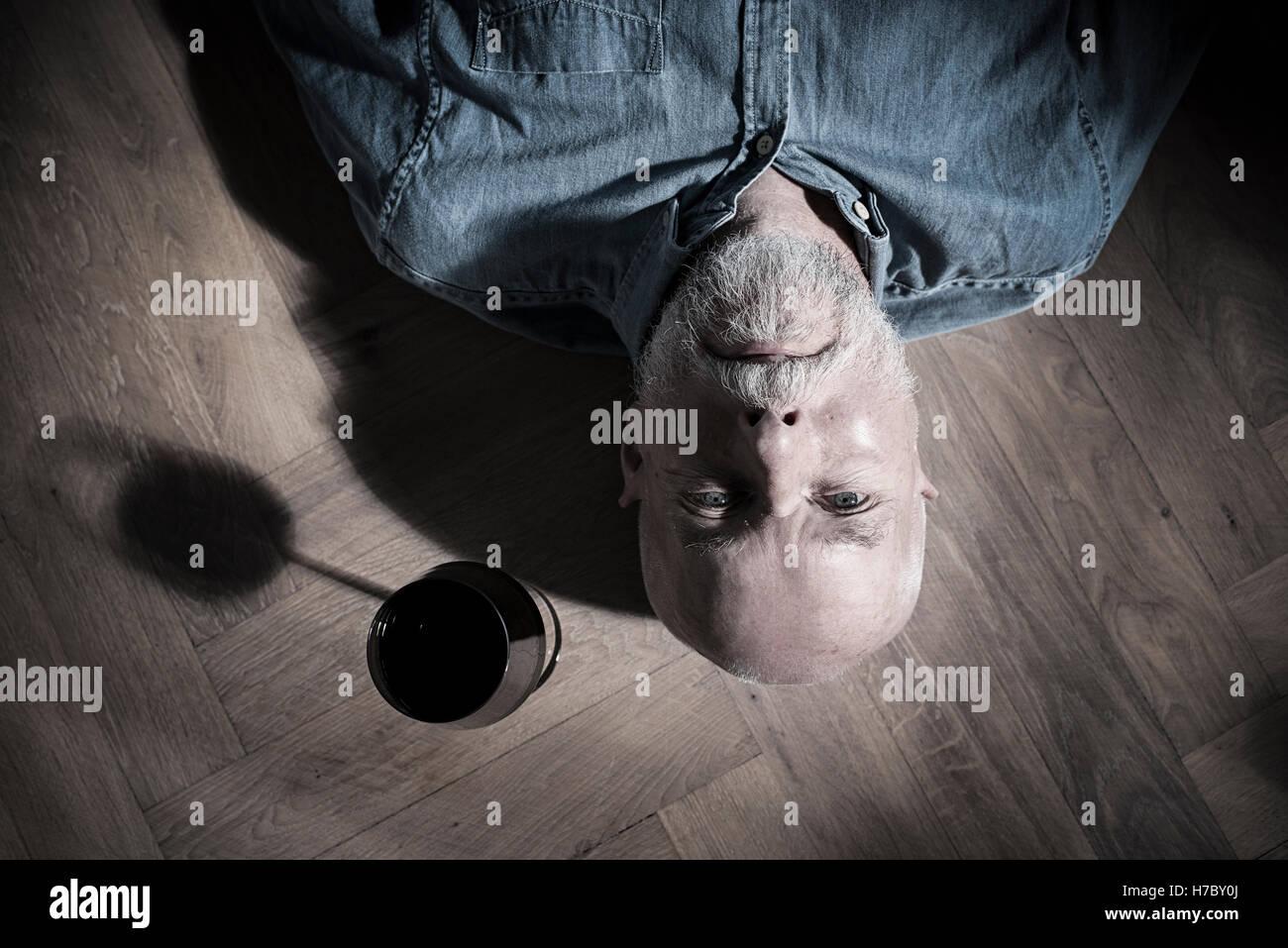Vieil homme se reposant sur le plancher avec un verre de vin sur le côté. Image conceptuelle de la solitude et de Banque D'Images