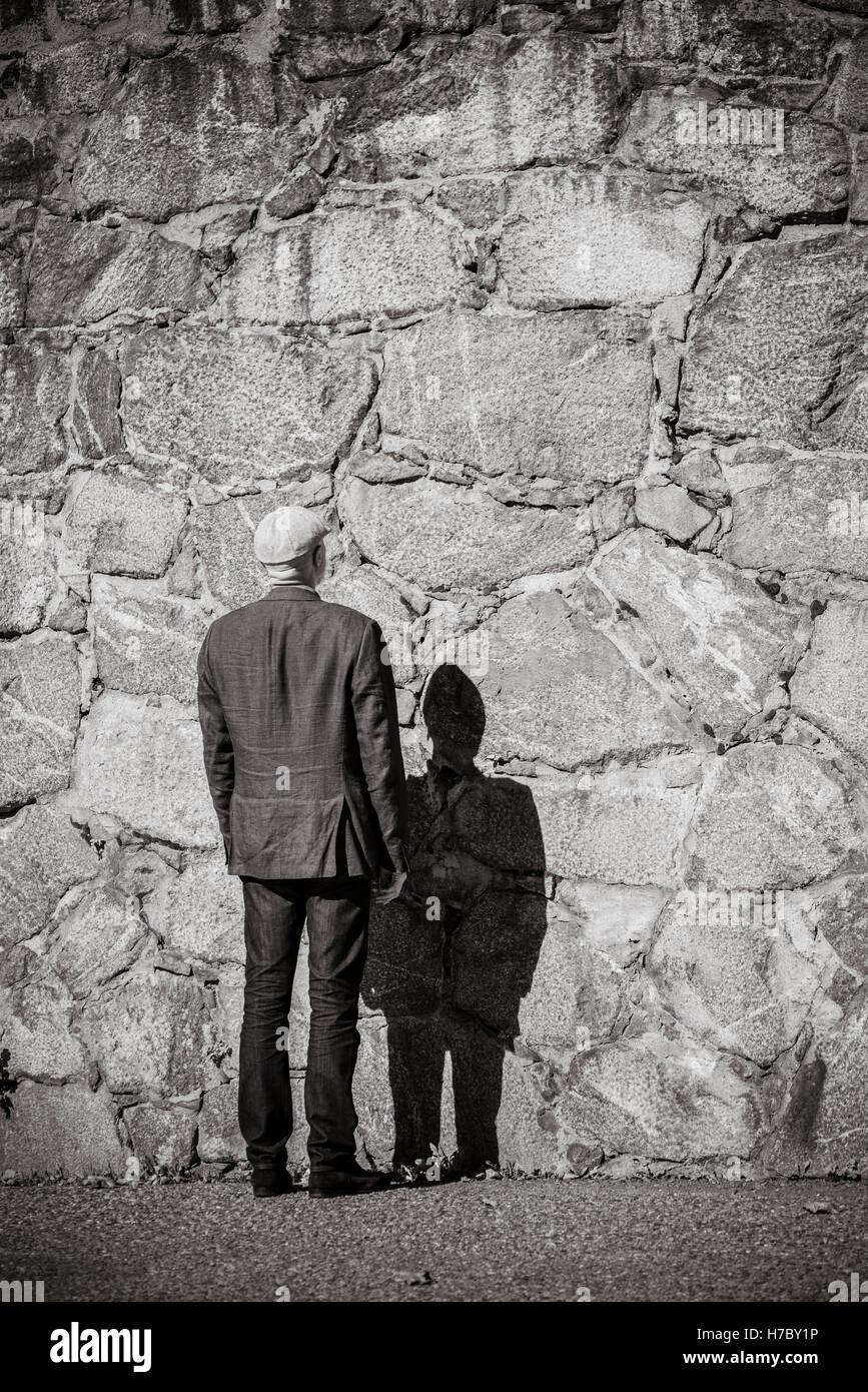Un vieil homme qui se tient en face de mur en pierre. Soleil et Ombre forte. Extérieur du bâtiment avec l'exemplaire Banque D'Images