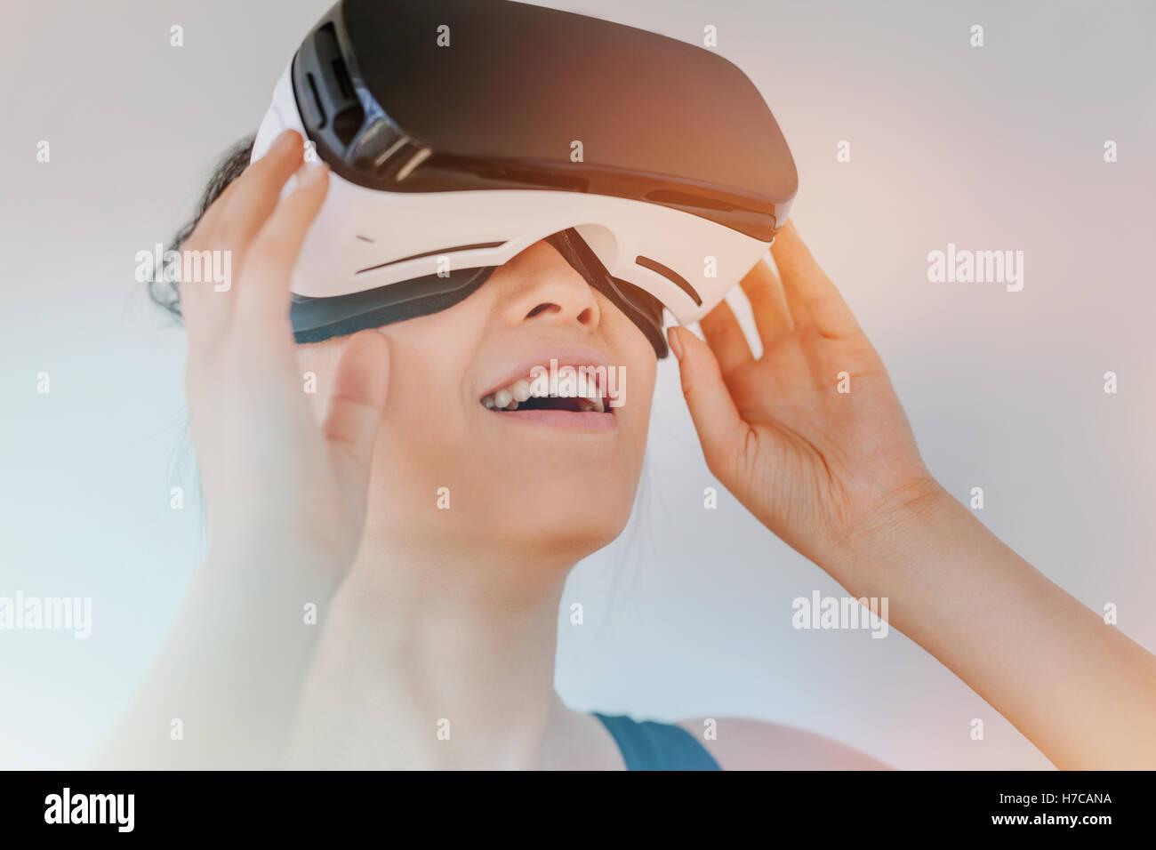 Close up of young woman in casque de réalité virtuelle à la recherche à l'objets. Modèle féminin avec des lunettes Banque D'Images