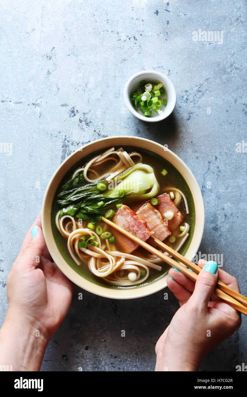 Les mains tenant un bol de soupe de nouilles Udon de porc.vue d'en haut Photo Stock