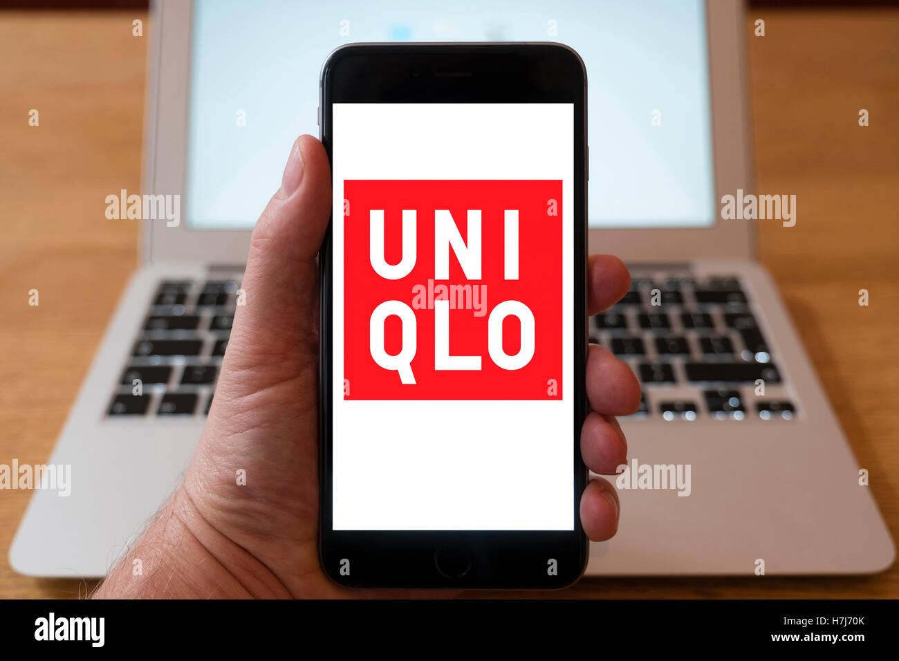 À l'aide d'iPhone smartphone pour afficher le logo d'UNIQLO , les Japonais wear concepteur, fabricant Photo Stock