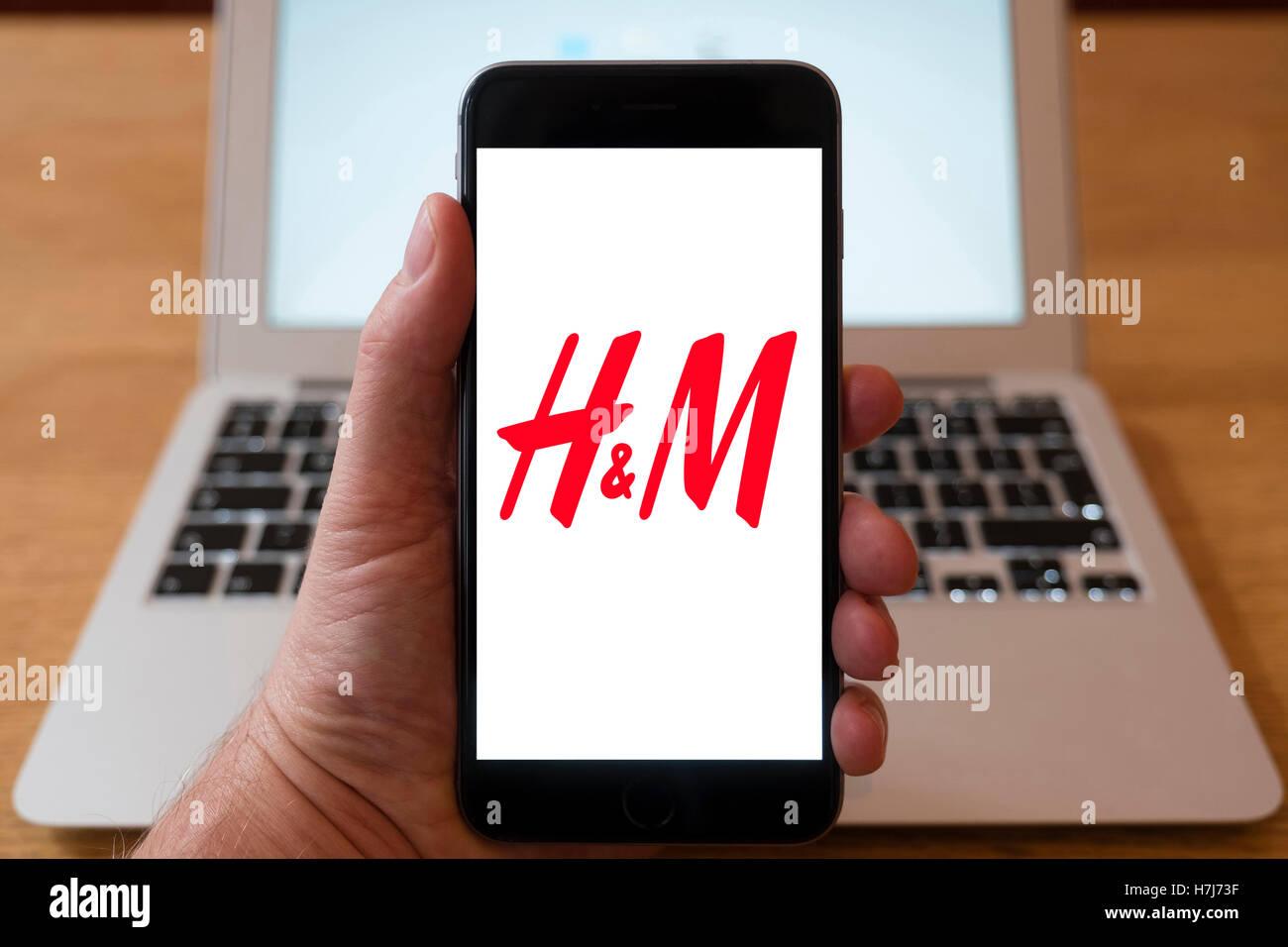 À l'aide d'iPhone smartphone pour afficher le logo d'H&M de haut détaillant de mode de Photo Stock
