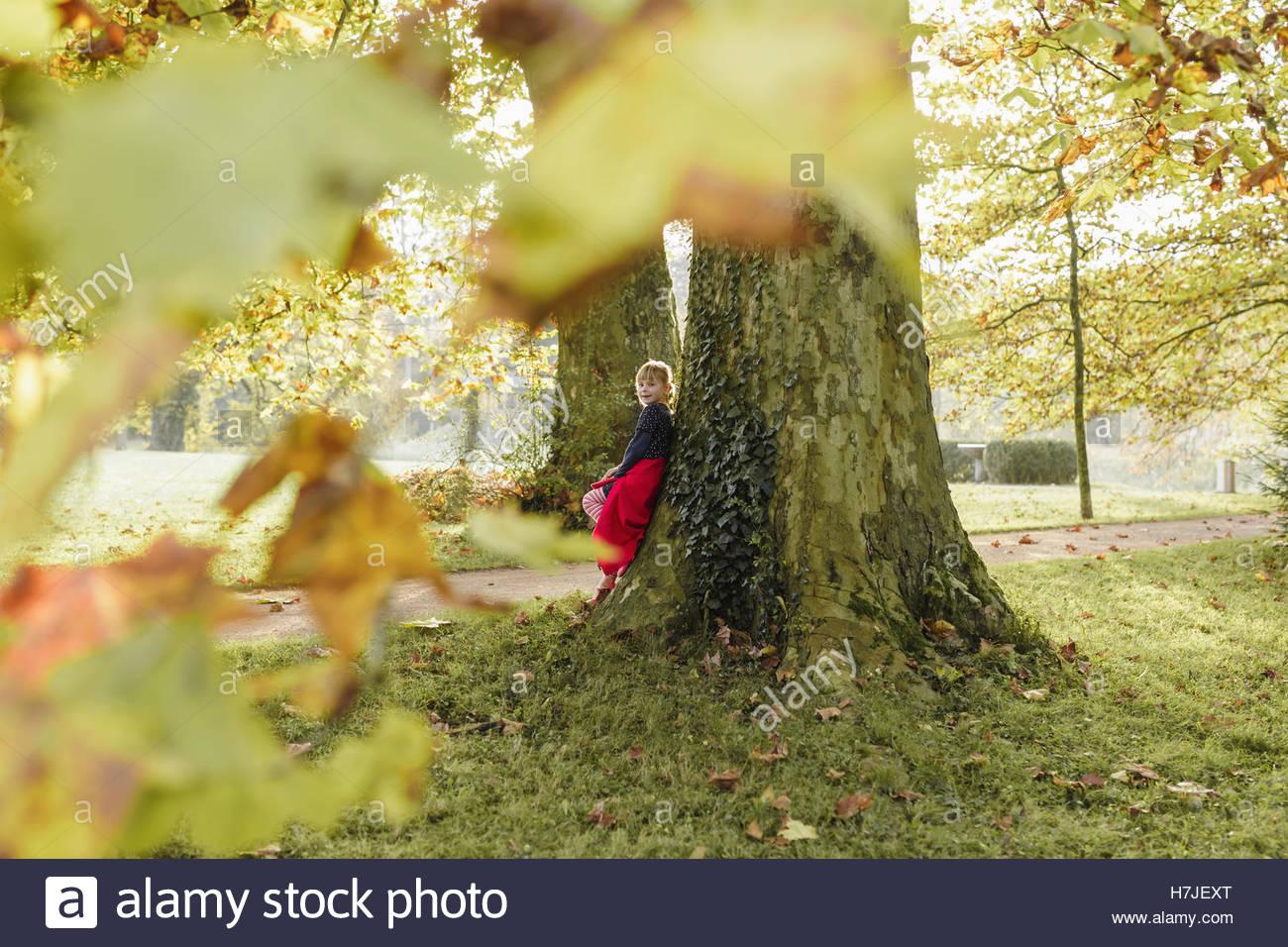 Lumière d'automne. Petite fille en manteau rouge appuyé contre un arbre en automne parc. Photo Stock