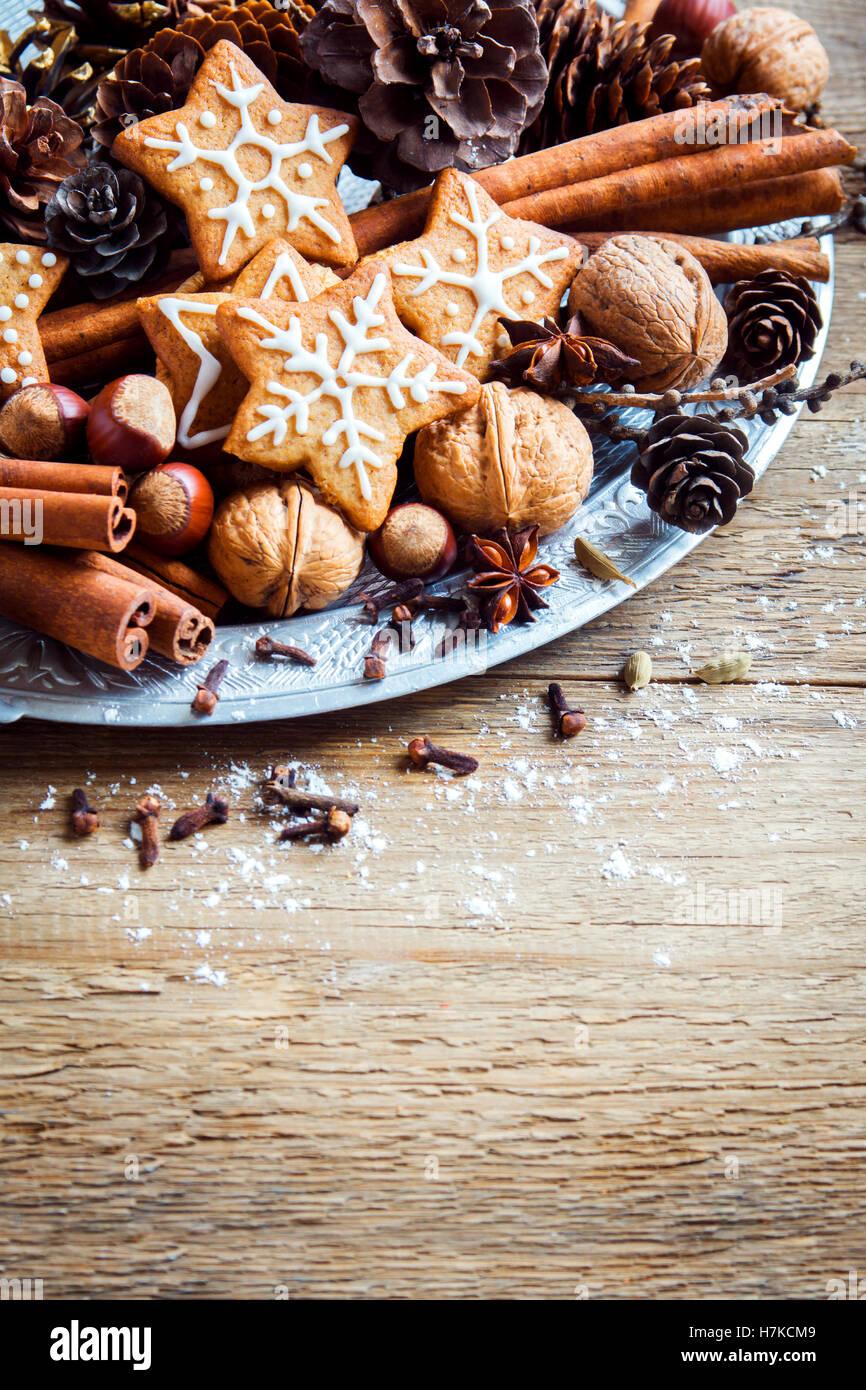 Décoration de Noël avec des biscuits au gingembre stars, cônes, noix et chocolat sur fond de bois Photo Stock
