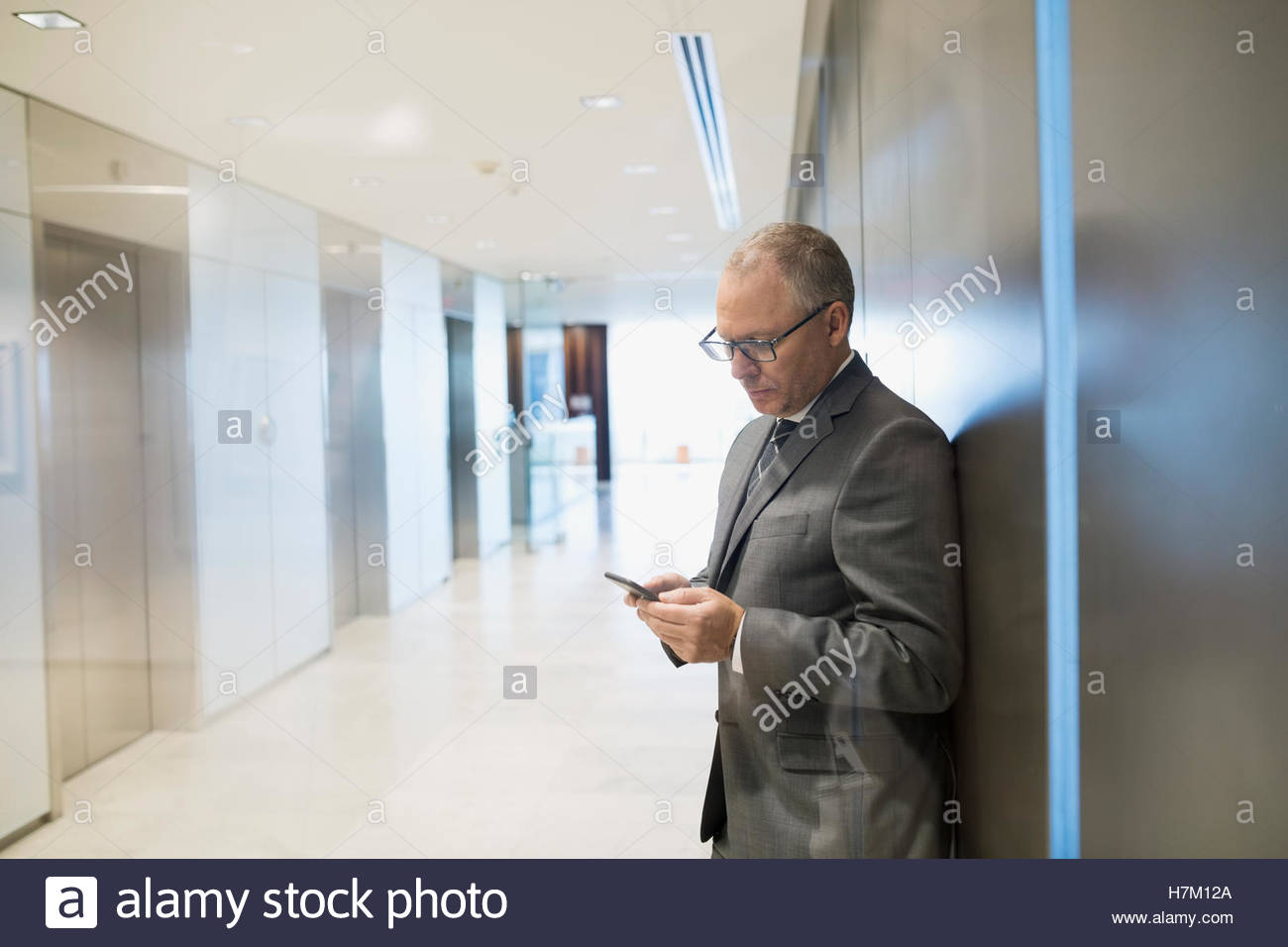 Businessman texting in office corridor Photo Stock