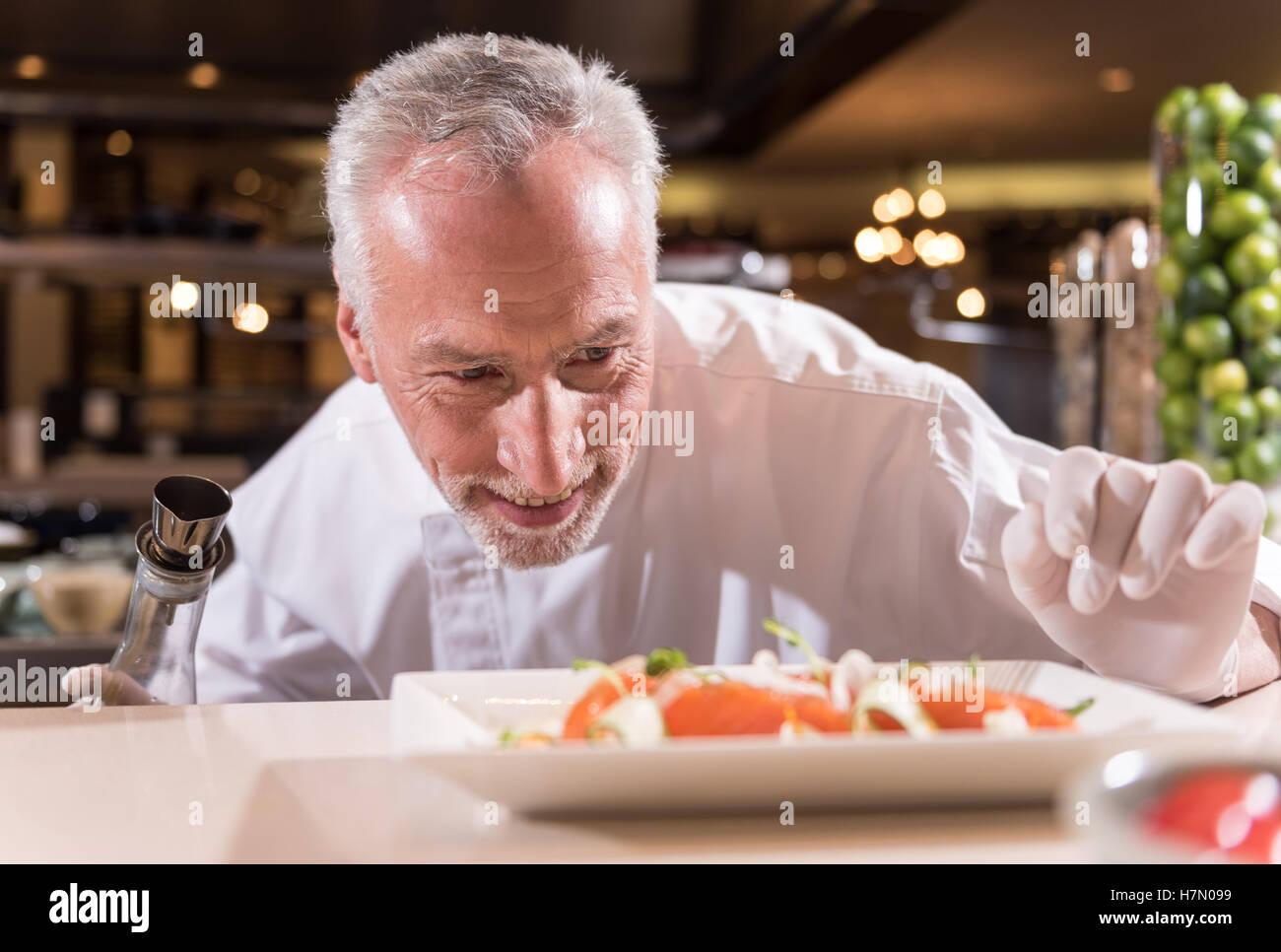 Heureux chef making les dernières corrections de sa lave Photo Stock