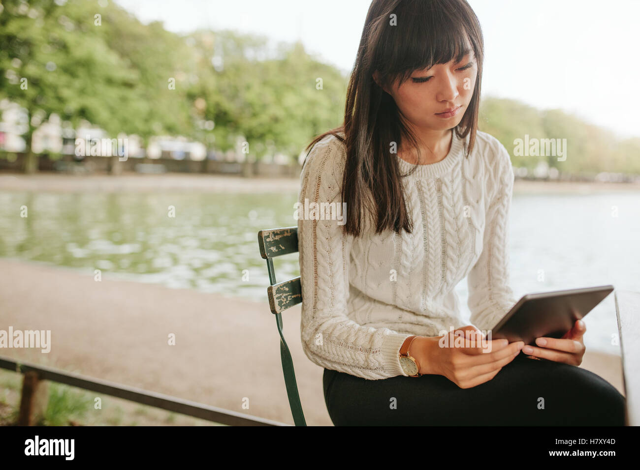 Shot of Chinese woman sitting on chair par l'étang et à l'aide de tablette numérique. Femme Photo Stock