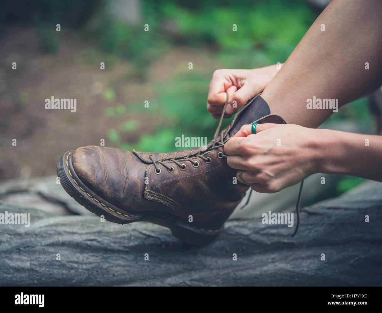 Une jeune femme est assise sur un journal dans la forêt et lie ses bottes Photo Stock