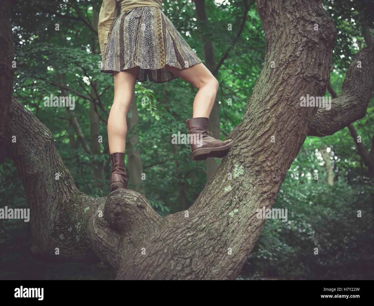 Une jeune femme portant une jupe est debout dans un arbre dans la forêt Photo Stock