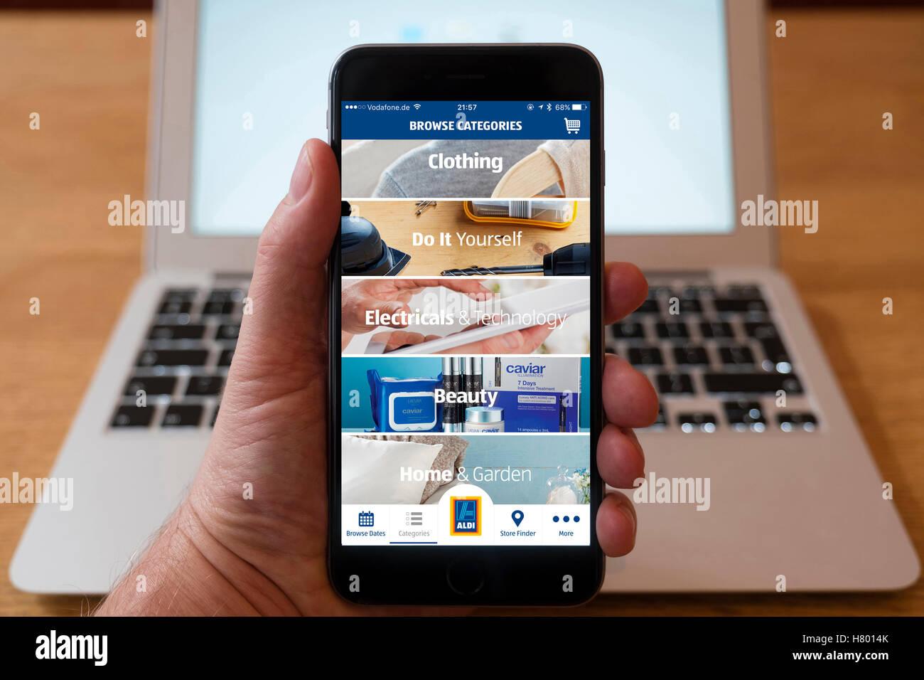 À l'aide d'iPhone smartphone pour afficher Aldi enseigne discount Boutique en ligne Photo Stock