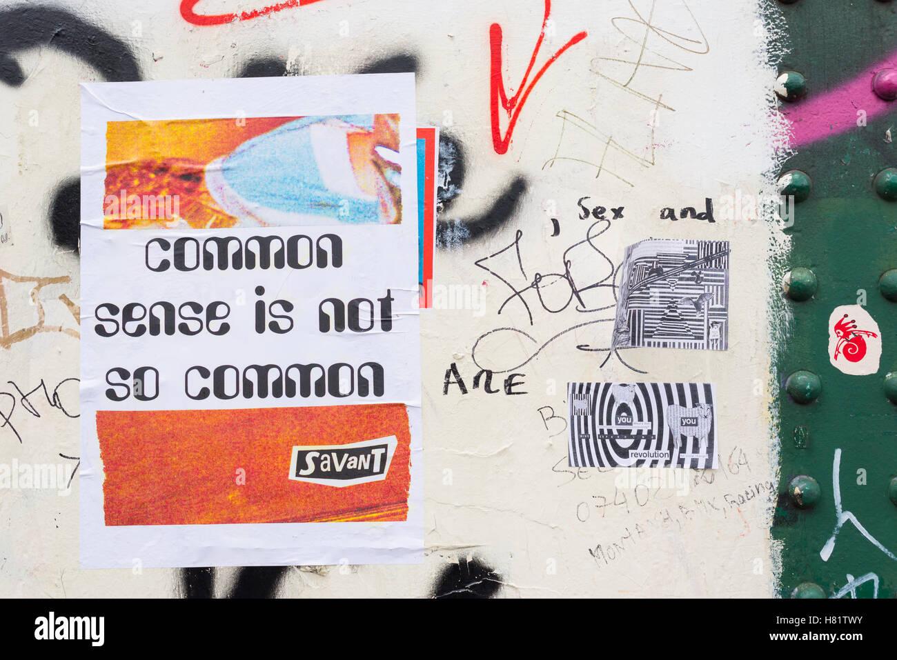 """Street art poster fixé au mur avec citation de Voltaire """"bon sens n'est pas si commun' à Photo Stock"""