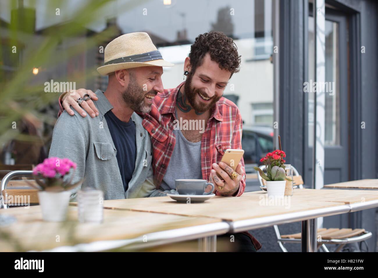 Couple Gay, assis dans le café téléphone partage Photo Stock