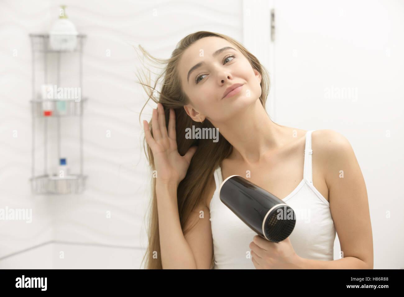 Belle jeune femme regardant le miroir sèche séchage Photo Stock