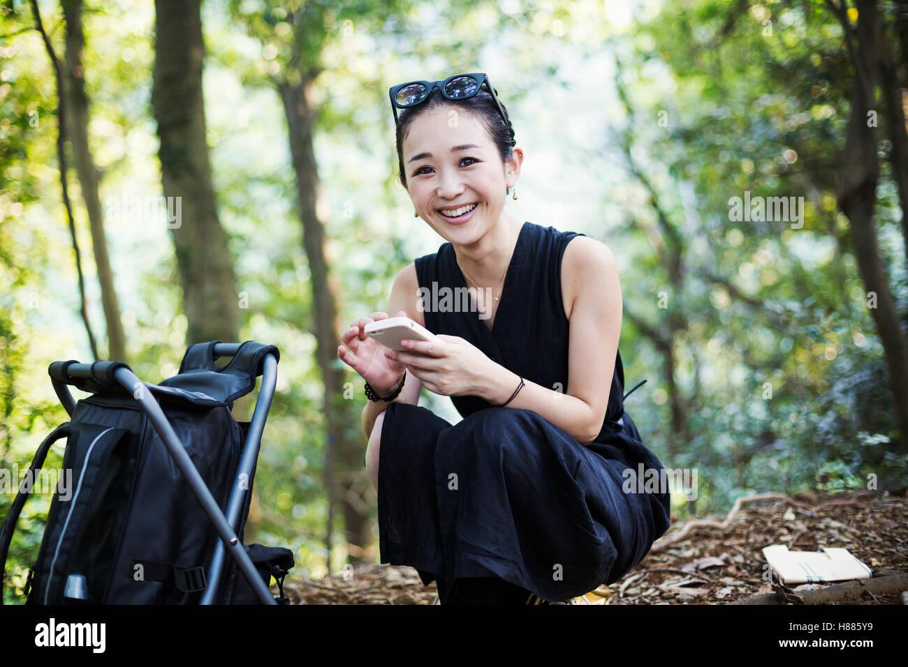 Jeune femme assise dans une forêt. Banque D'Images