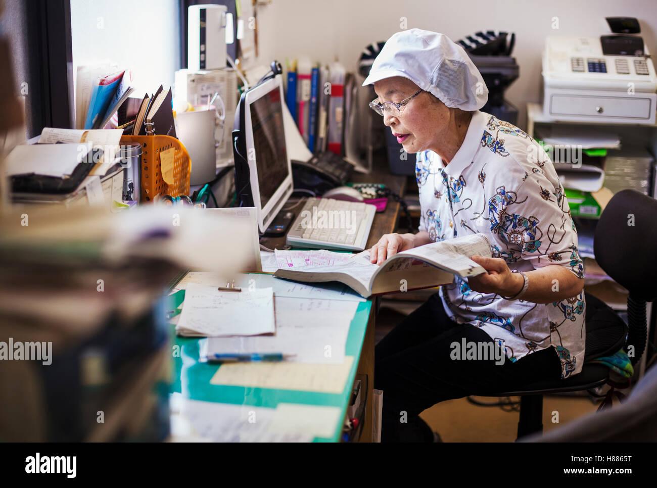 Une femme mature à un bureau de l'office d'une unité de restauration rapide et de nouilles en Photo Stock