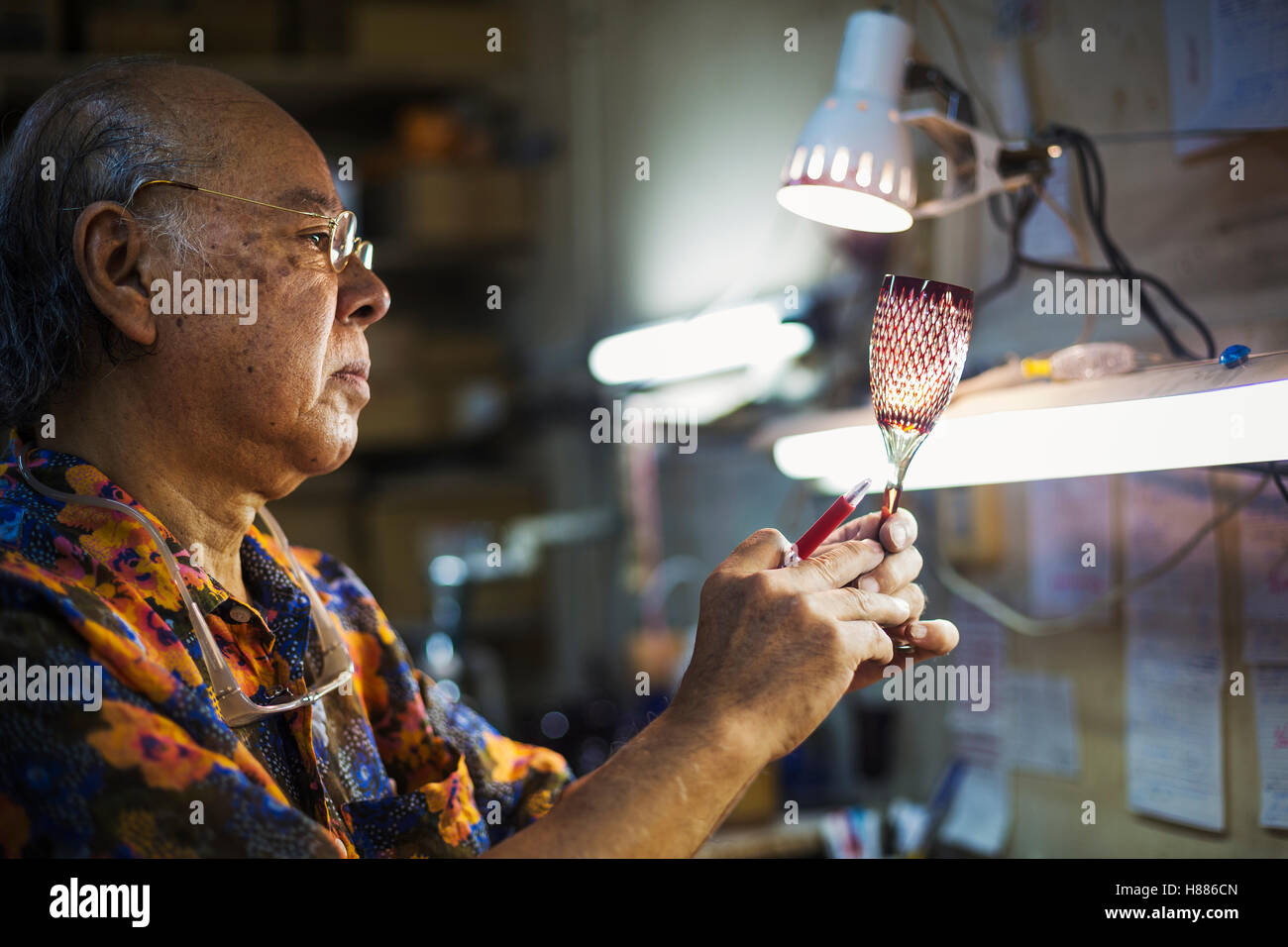 L'atelier verrier studio, l'homme l'inspection de verre à vin rouge avec décoration en verre Photo Stock