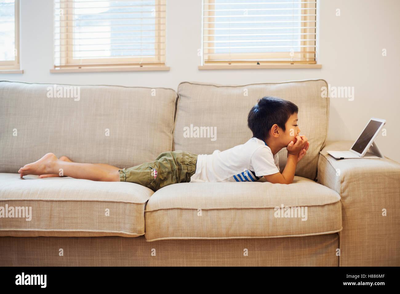 Maison de famille. Un garçon couché sur un canapé devant une tablette numérique. Photo Stock