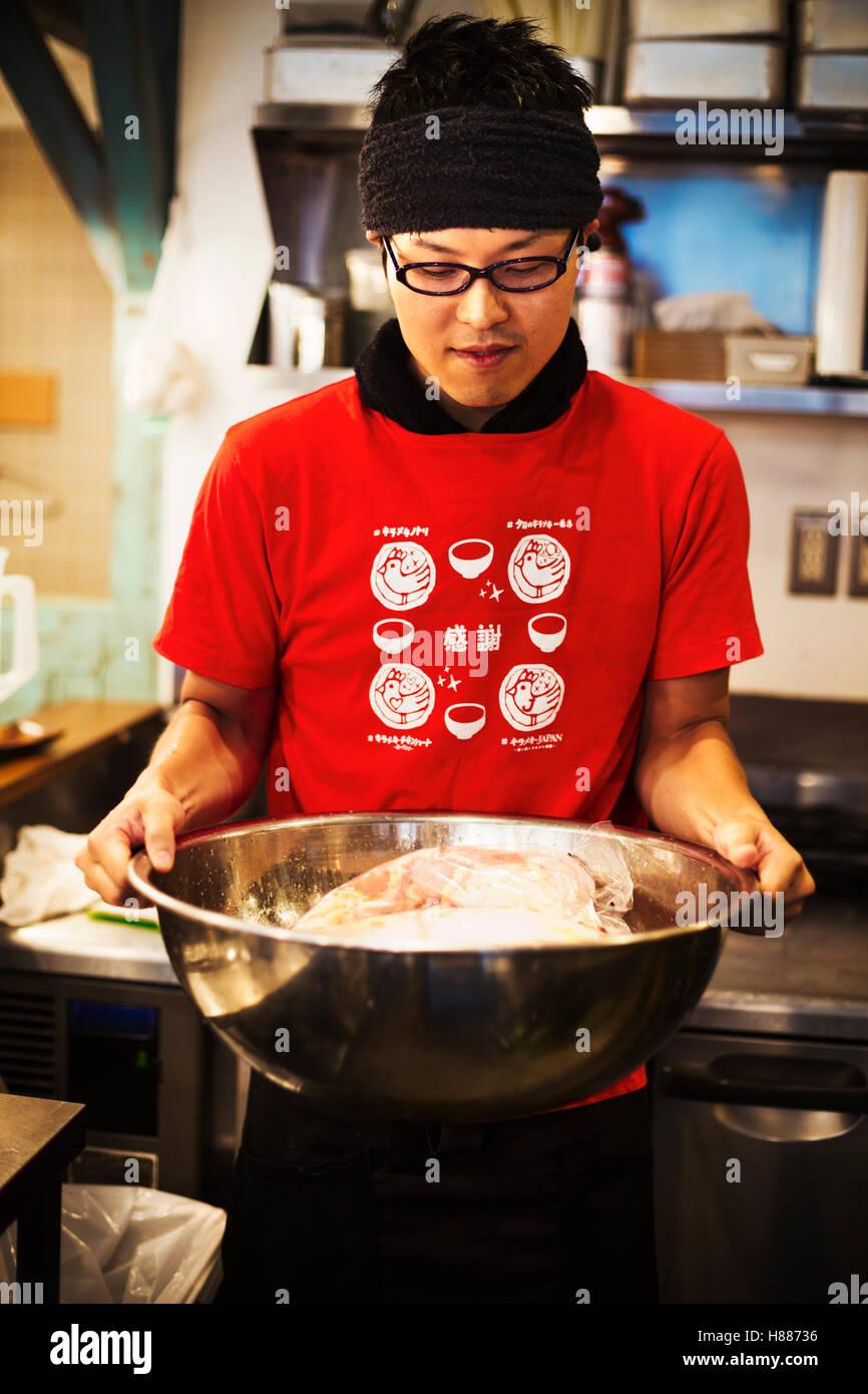 La boutique de nouilles ramen. Un chef cuisinier prépare un grand bol en métal de bouillon avec les ingrédients Photo Stock