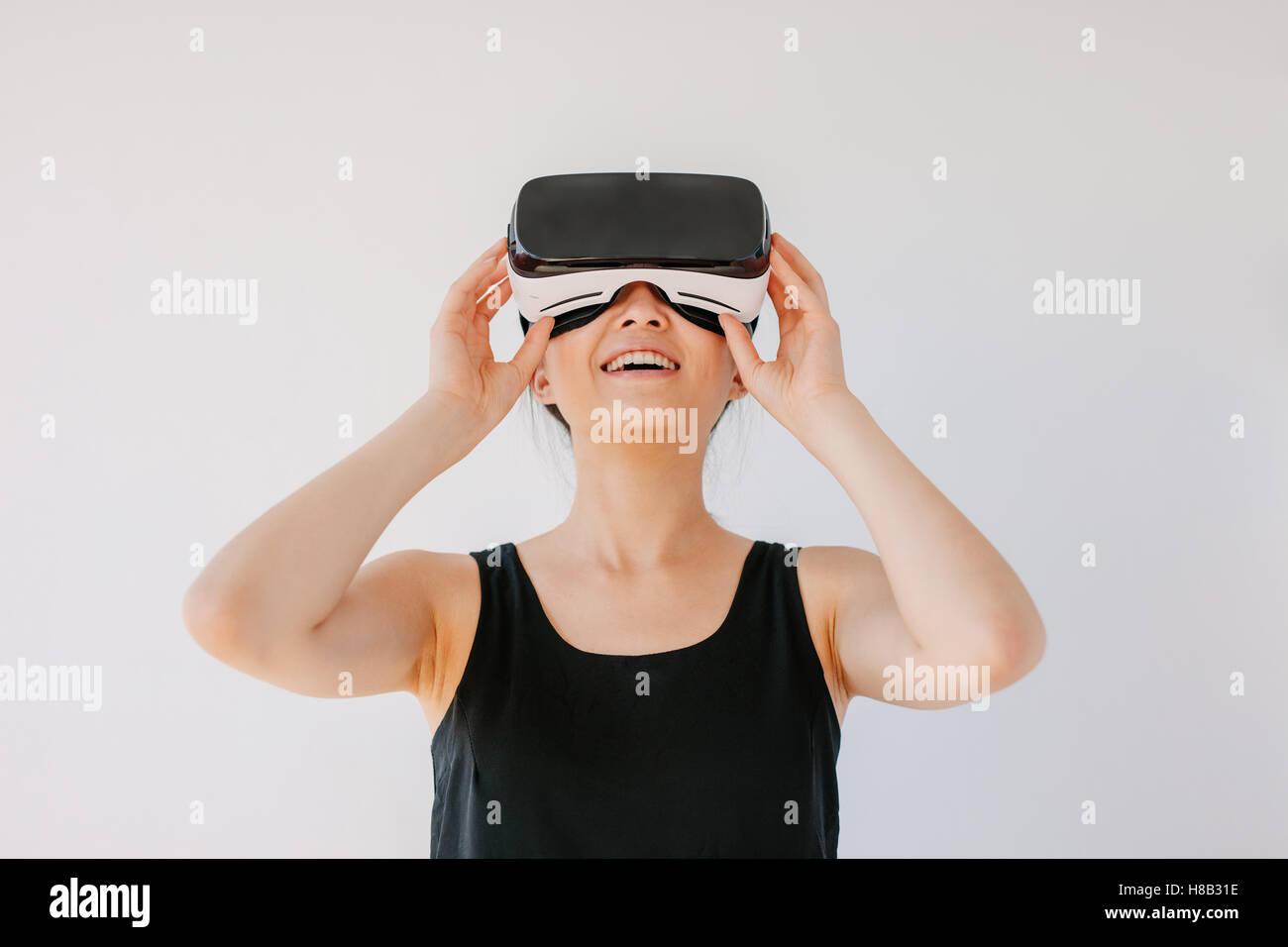 Coup de jeune femme en utilisant le casque de réalité virtuelle et souriant contre fond gris. Happy female mannequin Banque D'Images