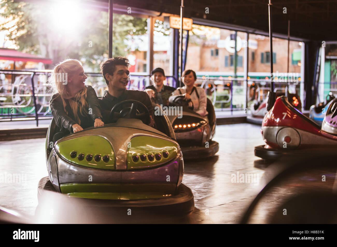 Les jeunes au volant de voitures pare-chocs à des expositions. Jeunes amis s'amusant équitation auto Photo Stock