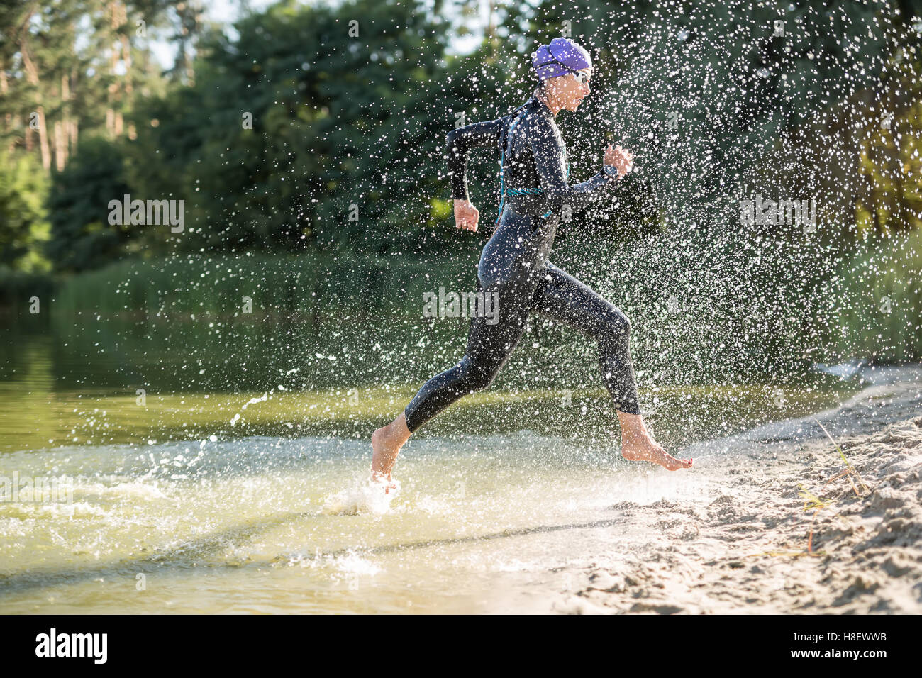 Sportive fille court sur le bord de l'eau Photo Stock