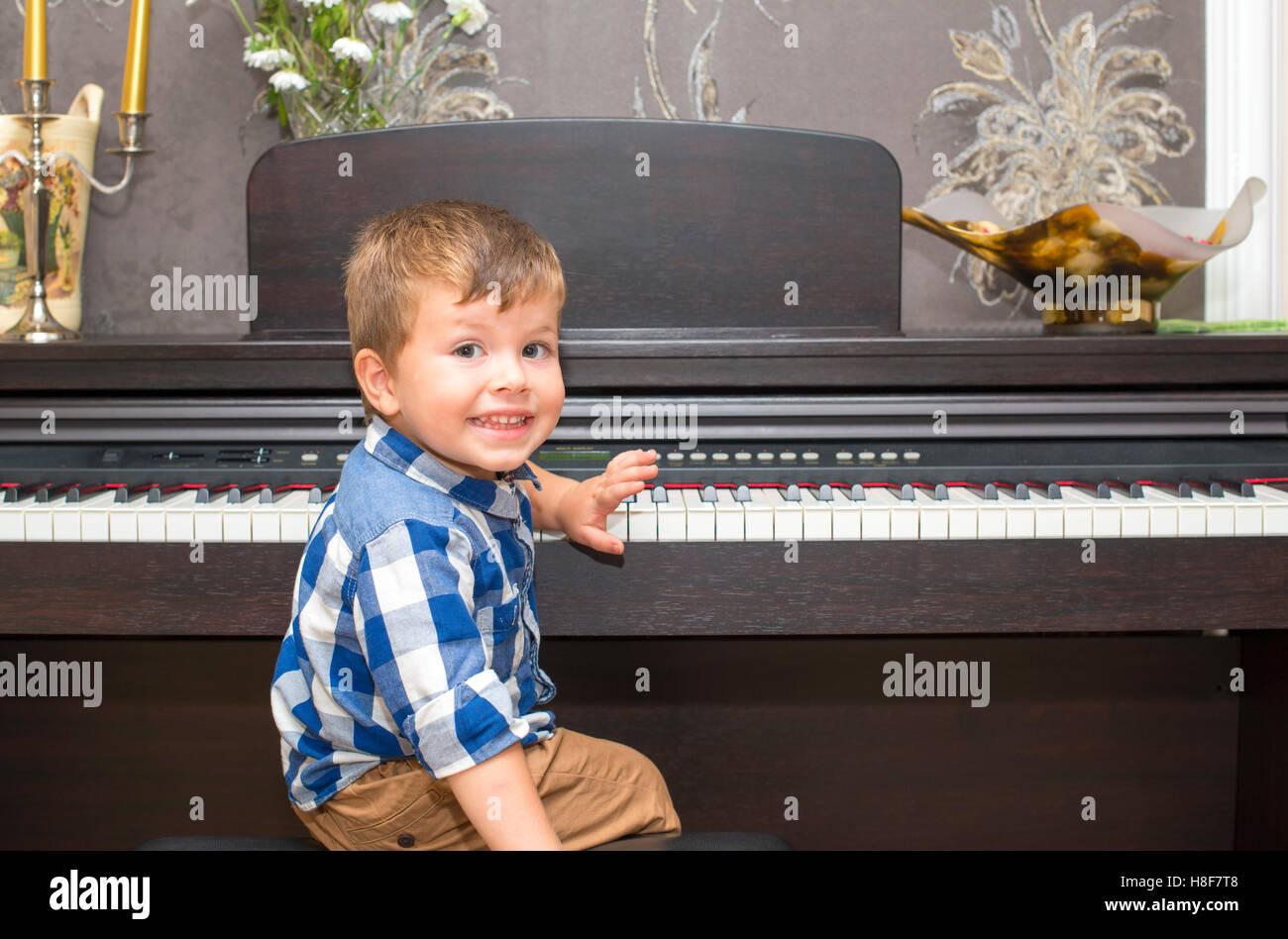 Heureux Garçon jouant du piano à la maison Photo Stock