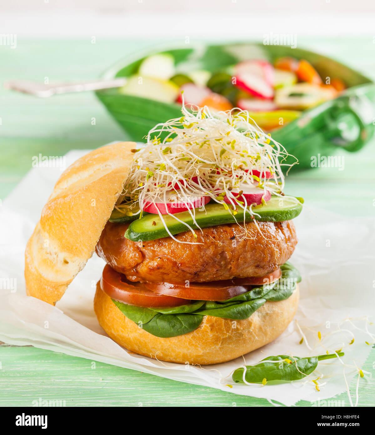 Un délicieux hamburger gastronomique avec des légumes frais: tomate, épinards, choux, radis Photo Stock