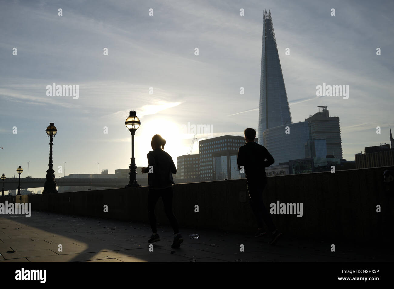 Un couple en marche le long de la rivière Thames, London Photo Stock