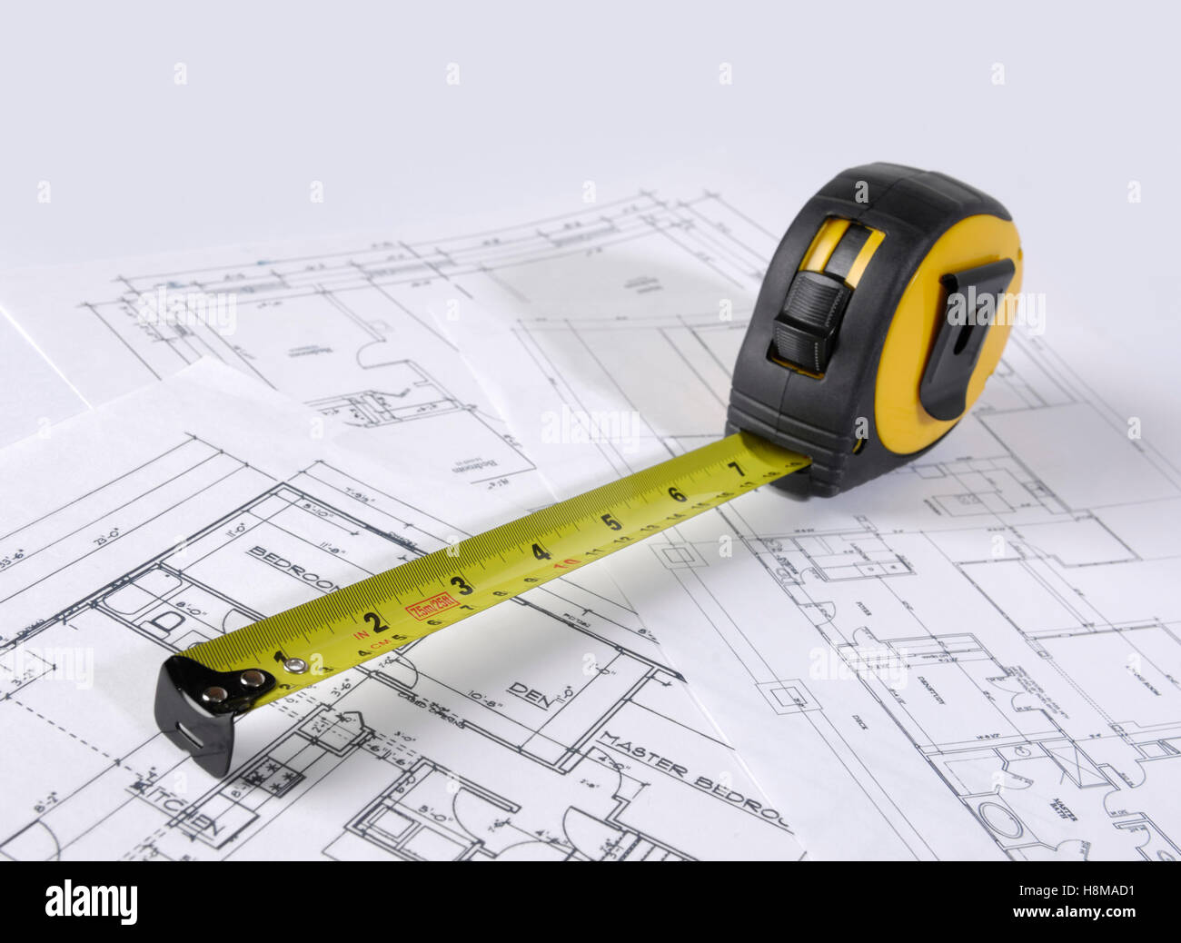 Ruban de mesure sur les plans de construction d'une maison Photo Stock