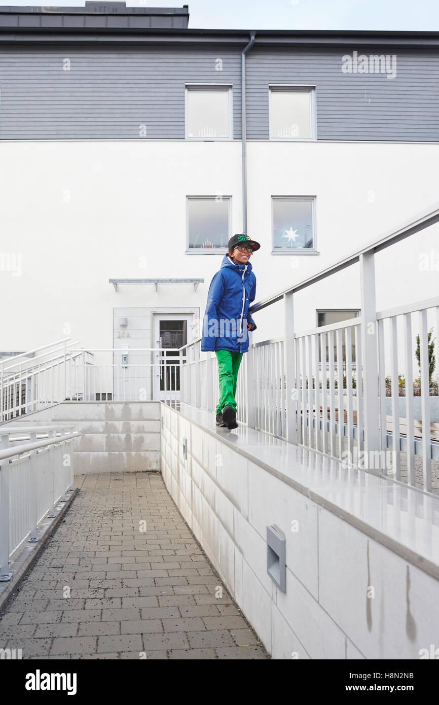 Boy (8-9) sur marche haut de wall by railing Photo Stock