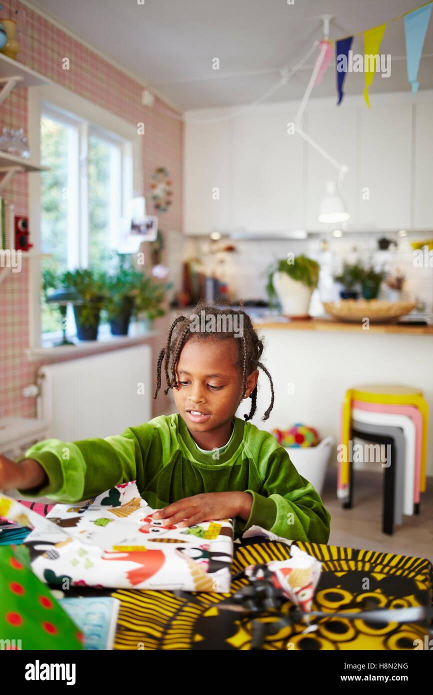 Girl (6-7) à jouer avec du papier décoratif dans la cuisine Photo Stock