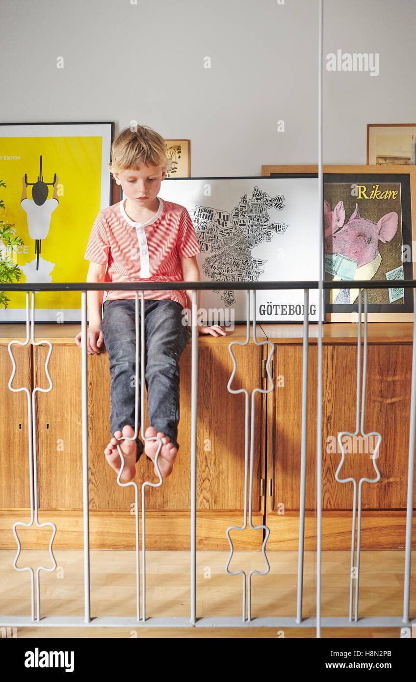 Garçon assis sur meuble avec photos derrière railing Photo Stock