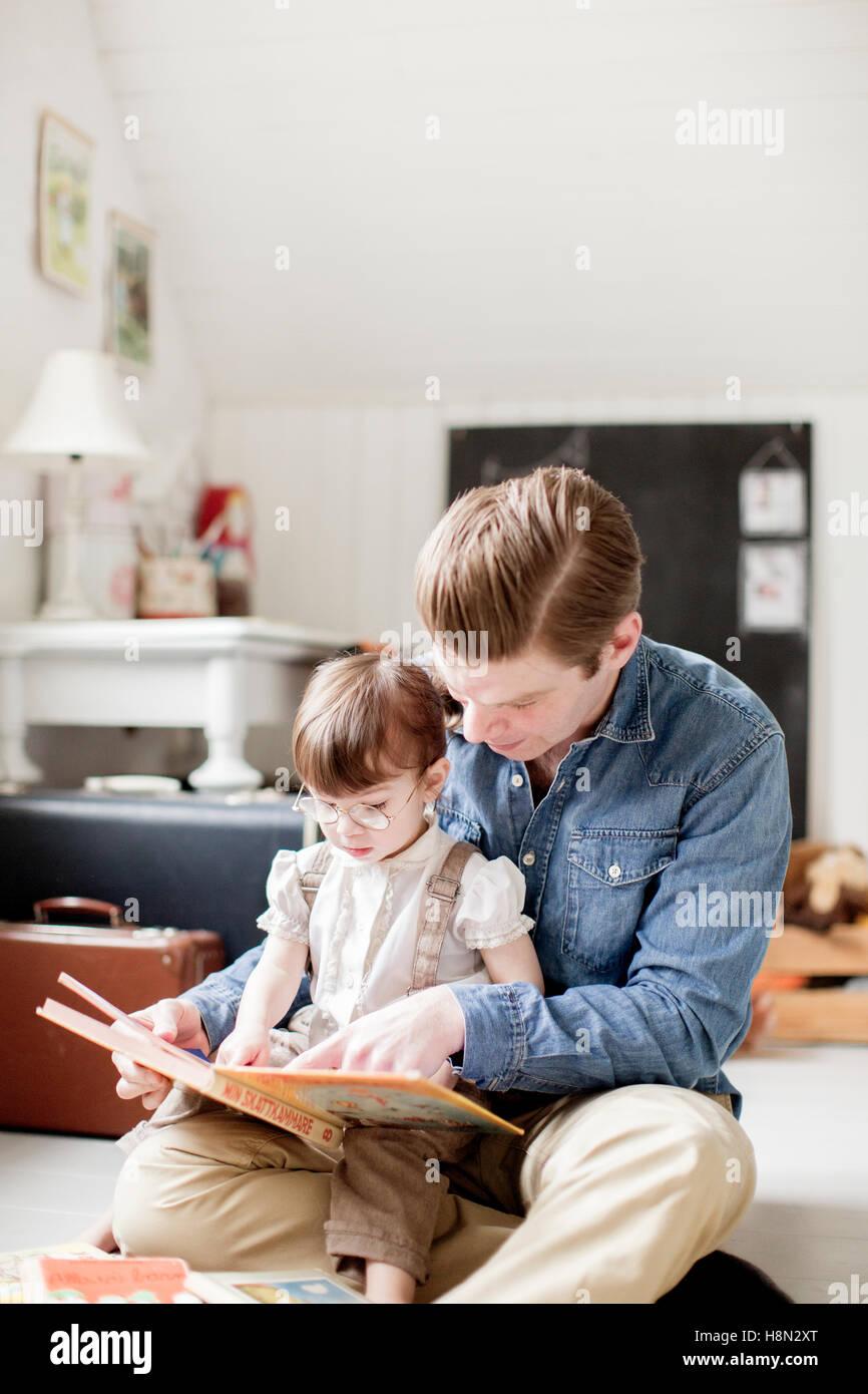Père la lecture avec sa fille (2-3) photo book Photo Stock