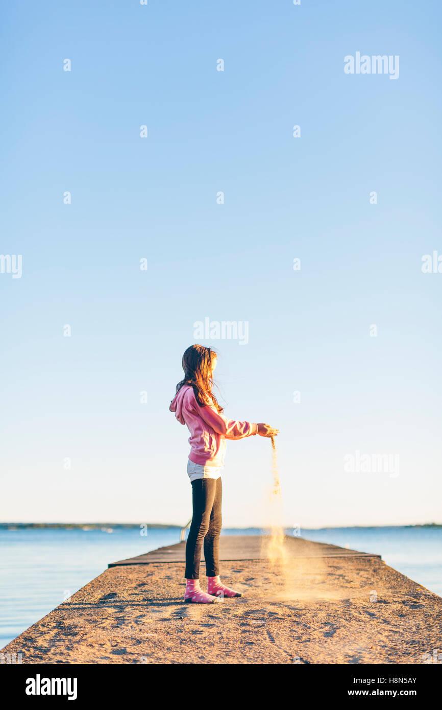 Girl (10-11) Versement au quai de sable Banque D'Images