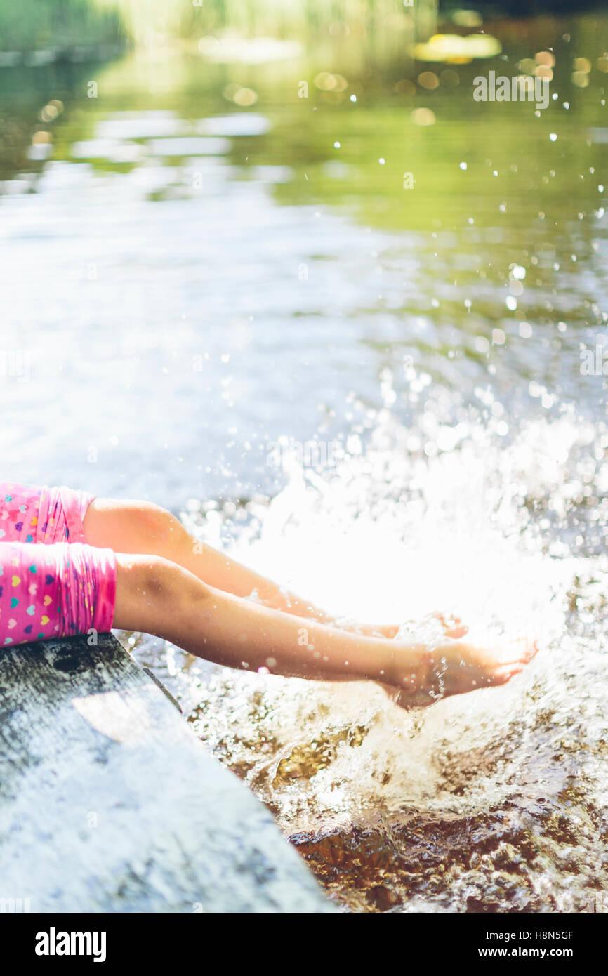 La section basse de girl (8-9) les projections d'eau avec les jambes Photo Stock