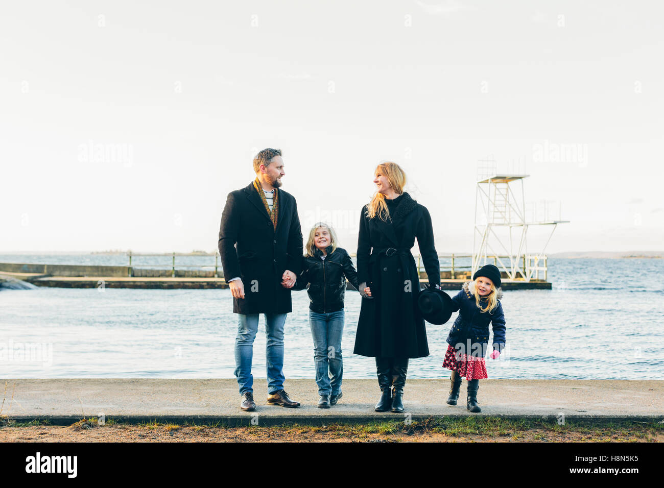 Les parents avec sa fille (4-5) et son (8-9) Comité permanent par la mer Photo Stock