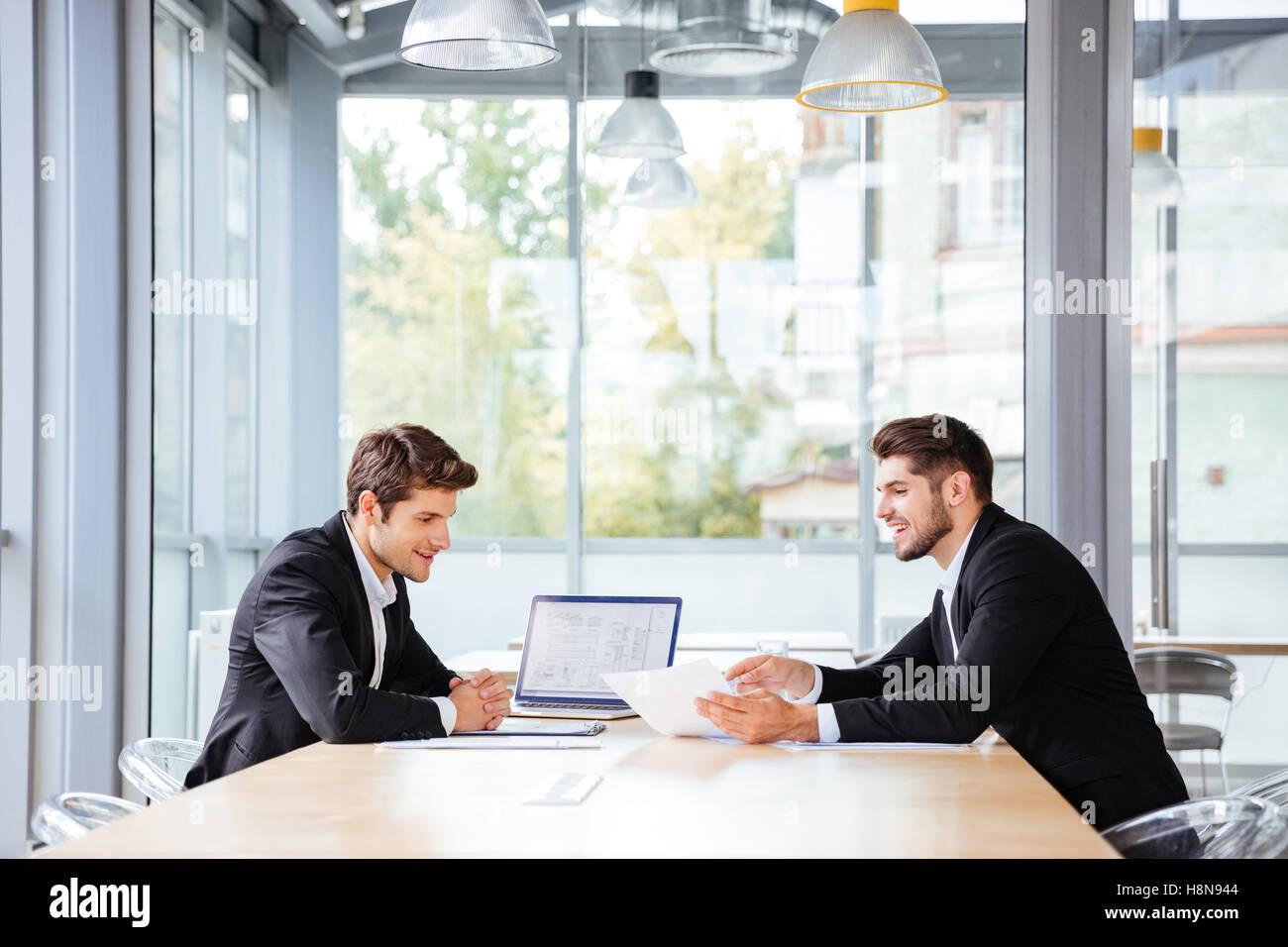 Deux jeunes hommes d'affaires heureux de travailler ensemble à l'aide de l'ordinateur portable sur business meeting Banque D'Images