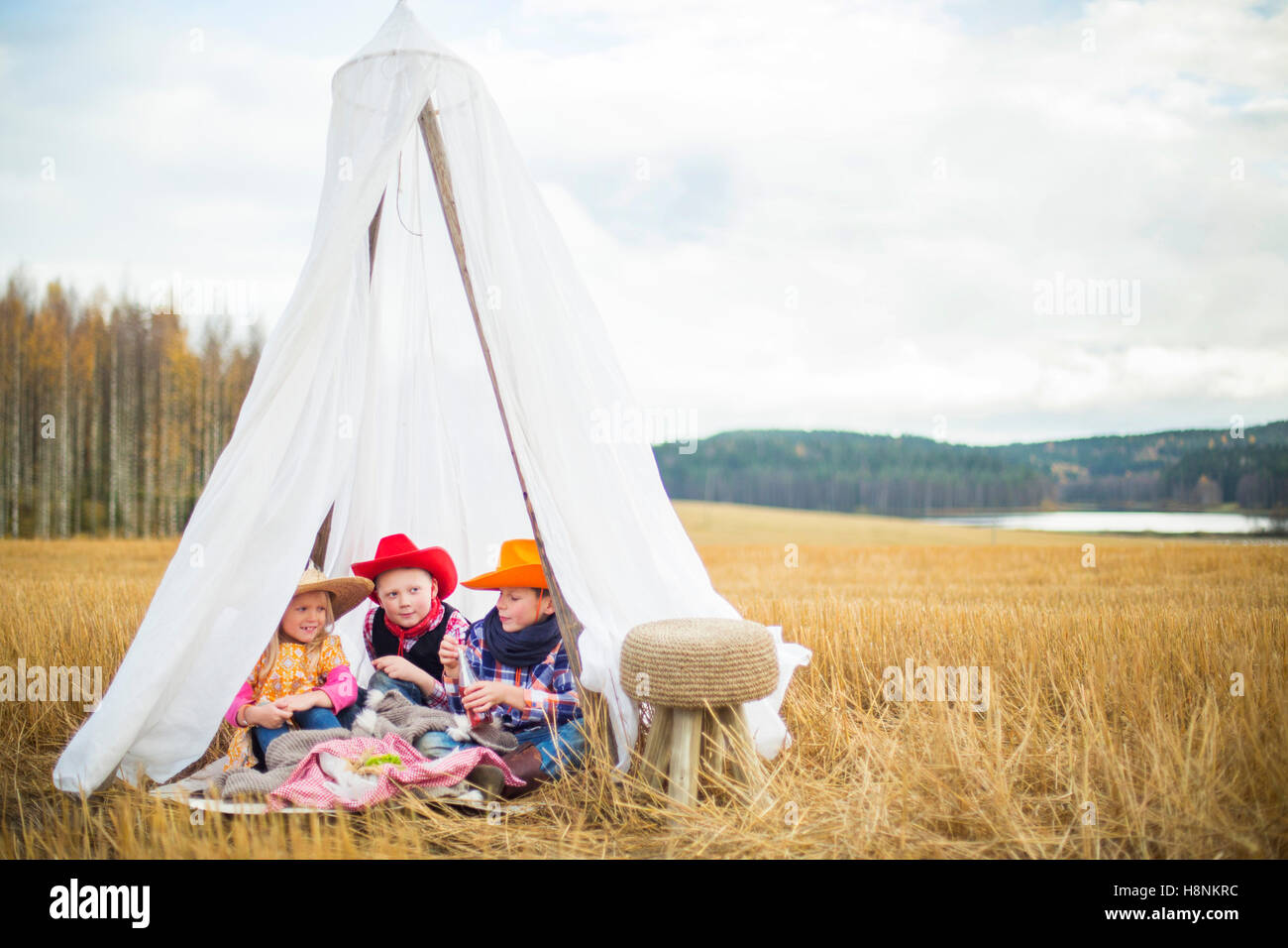Enfants (8-9) portant des chapeaux de cow-boy sitting in tent Photo Stock